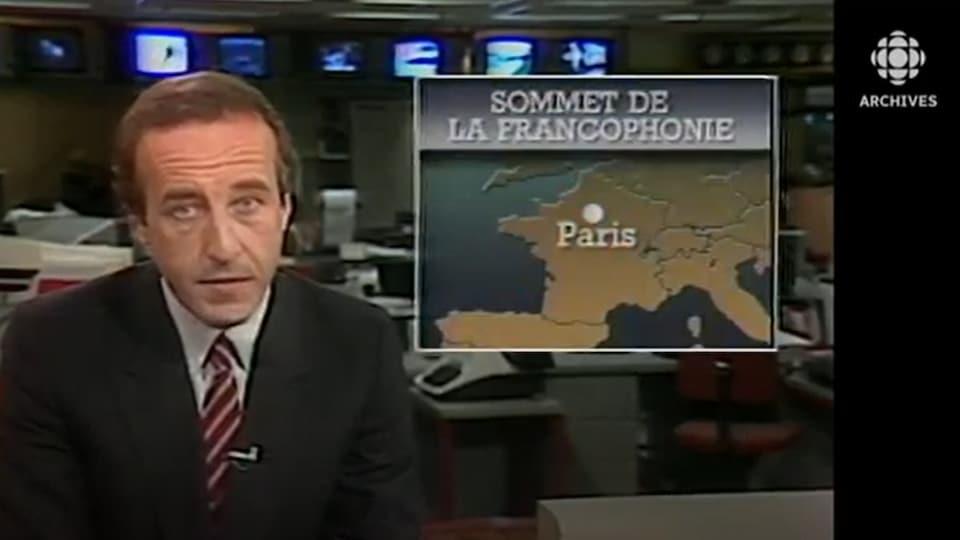 À côté de l'animateur Bernard Derome, on voit une carte qui indique la position de la ville de Paris en France.