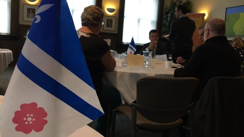 Le drapeau franco-albertain et des gens assis à une table.