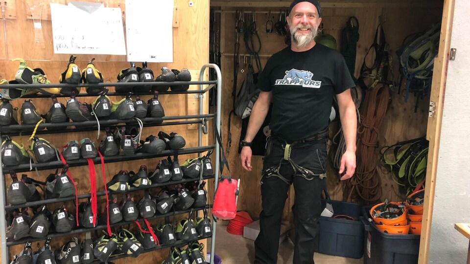 Fred Fournier, co-propriétaire de l'entreprise Attitude nordique, dans un local avec des souliers d'escalade