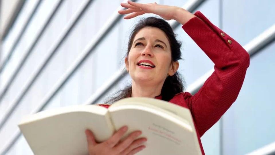 Une femme qui lit un livre en faisant un mouvement de bras.
