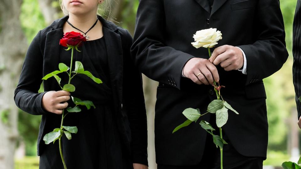 Une famille endeuillée sur un sentier se rend à des funérailles. Les deux enfants et les deux adultes tiennent tous une rose à la main. On ne voit pas leurs visages.