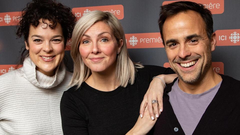 Les trois artistes sourient à la caméra.