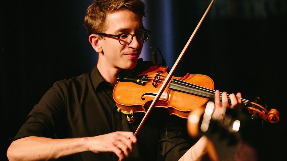 Un jeune homme joue du violon.