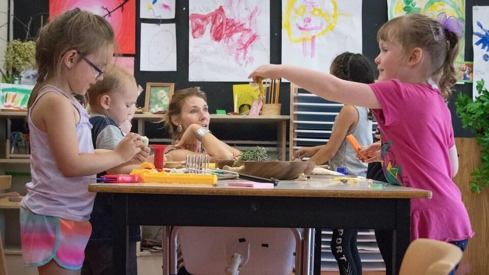 Des enfants jouent avec leur éducatrice à une table.
