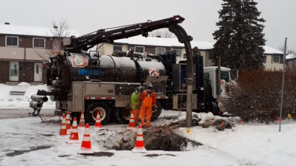 Deux employés sont devant un camion et réparent la conduite de gaz.