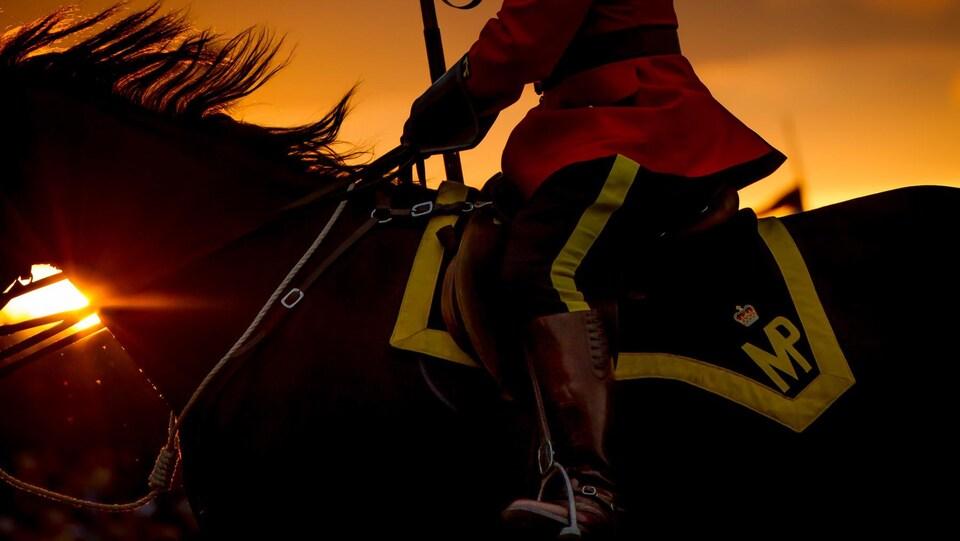 Un policier de la GRC à dos de cheval, avec le soleil se couchant en arrière-plan.