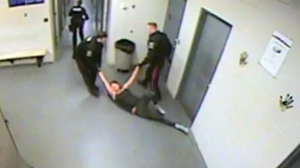 Deux agents traînent Genesta Garson par les bras sur un sol de ciment.