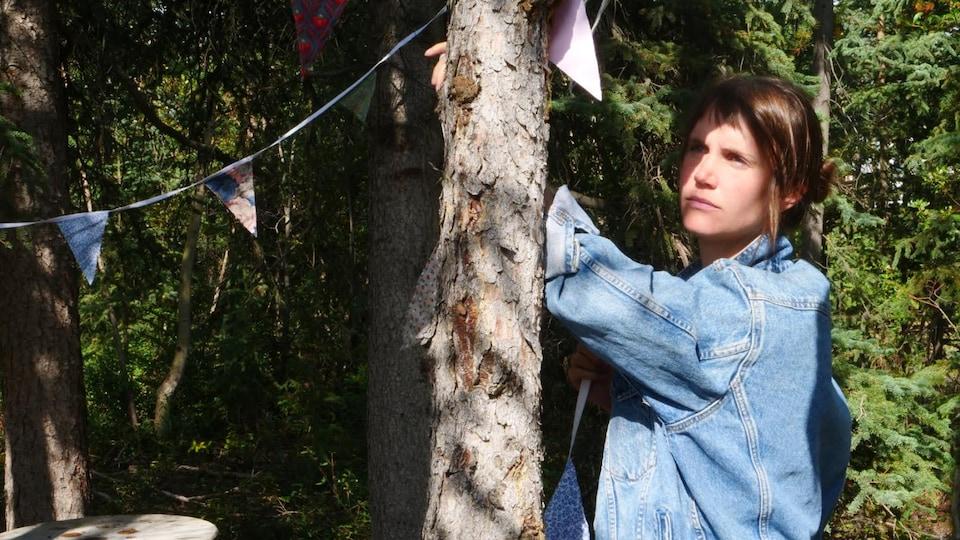 arbres, fanions et jeune femme en blouson Levi's bleu ciel dans une forêt boréale semi-éclairée