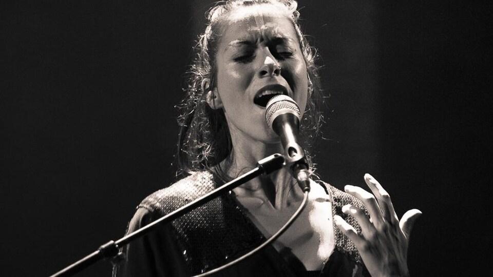 Jeune dame aux longs cheveux, yeux fermés, chante dans un microphone.