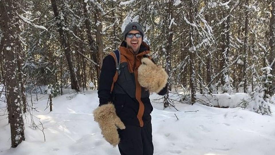 Un homme en raquette dans le bois en hiver.