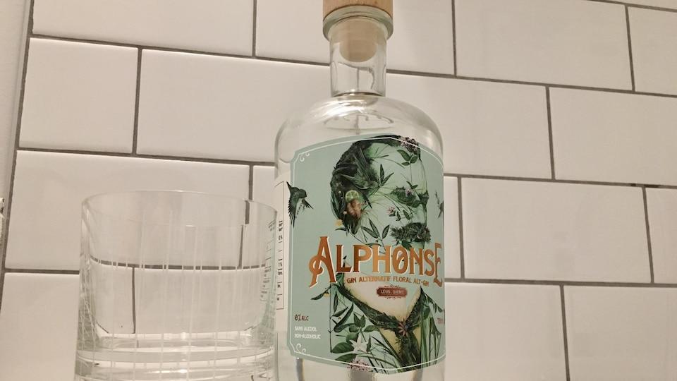 Une bouteille de gin avec une étiquette verte à côté d'un verre vide.