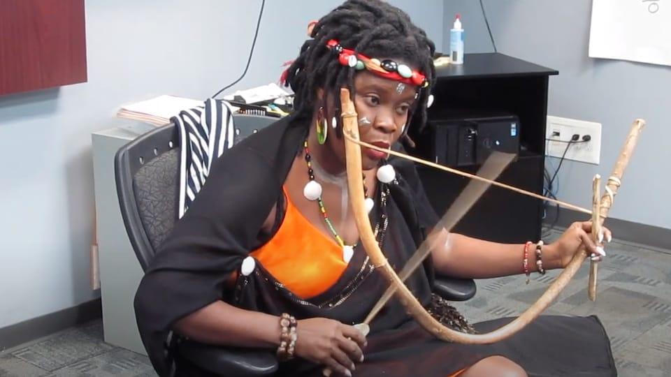 Sa bouche est posée sur une corde épaisse tendue entre les deux extrémités d'un bâton courbé.