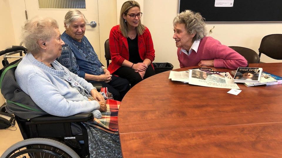Quatre femmes, trois sont âgées, dont une en fauteuil roulant, discutent à table