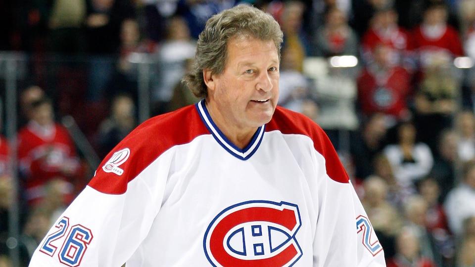 Pierre Bouchard porte un chandail des Canadiens de Montréal et un bâton de hockey sur la patinoire du Centre Bell.