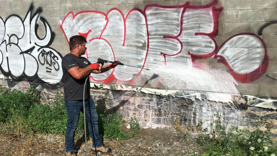 Un homme en train d'asperger un tag sur un mur pour le faire disparaître.