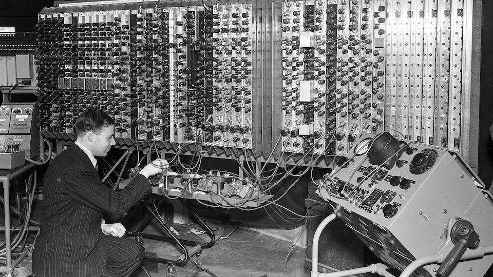Photo en noir et blanc d'un homme qui travaille, accroupi, sur un ordinateur des années 1950.