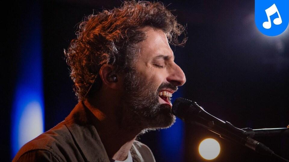 Le chanteur Louis-Jean Cormier, de profil, chante dans un microphone.