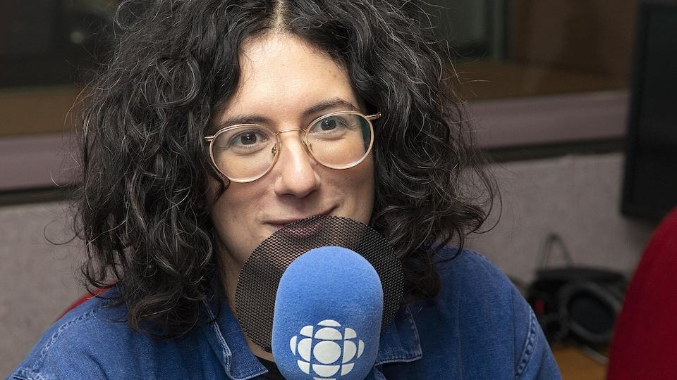 Dans un studio, une femme sourit légèrement devant un micro.
