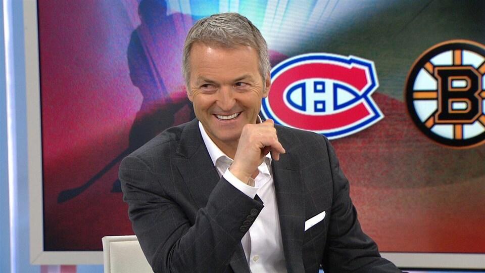 Un homme sourit devant un écran de télévision affichant le logo des Canadiens de Montréal et des Bruins de Boston.