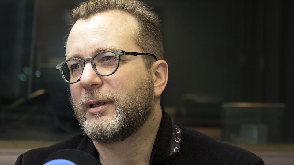 Un homme avec des lunettes parle devant un micro.