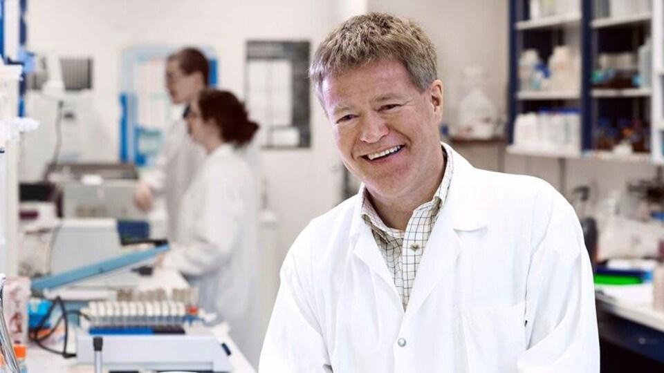 Un homme souriant et portant un sarrau blanc se trouve dans un laboratoire de recherche scientifique.