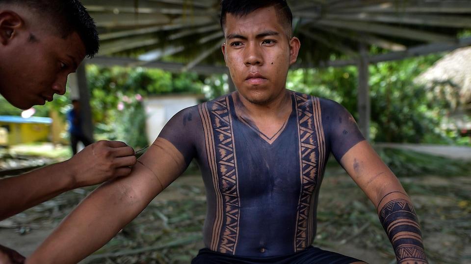 Un tatoueur tient un pinceau près du bras d'un autochtone Embera, dont le torse et les bras sont recouverts de peinture bleue.