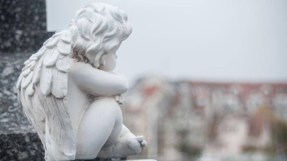 Un ange de pierre est assis sur une pierre tombale dans un cimetière.