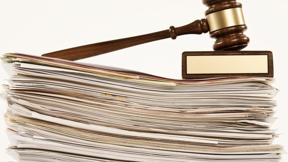 un marteau de juge est posé sur une grosse pile de dossiers.