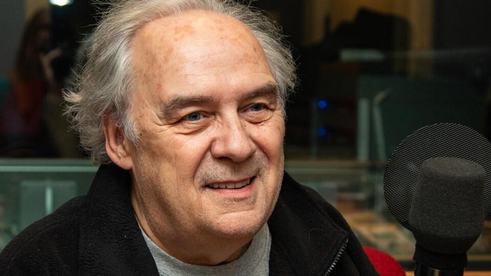 Un homme sourit devant un micro de radio.