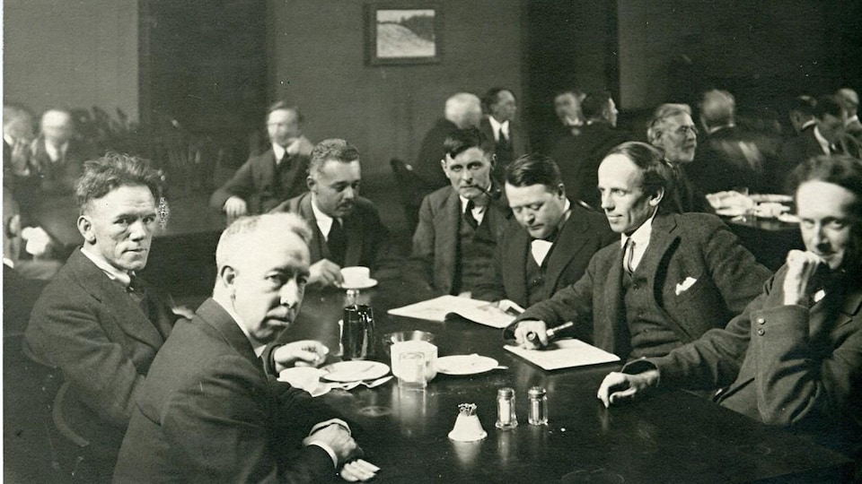 Sept hommes en complet discutent autour d'une table.