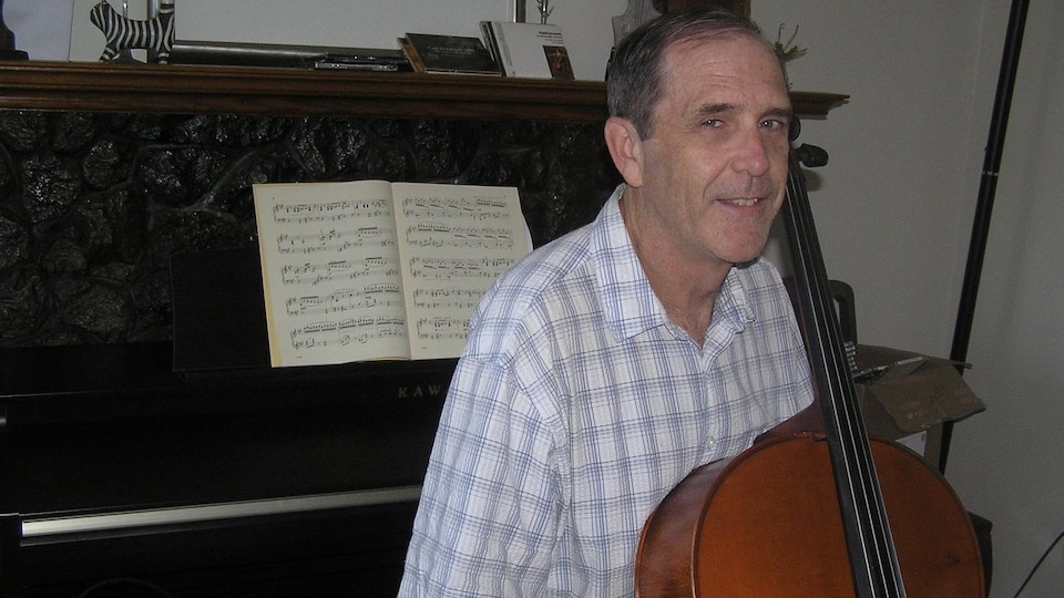Un homme souriant tenant son violoncelle est assis devant un piano sur lequel repose des feuilles de musique.