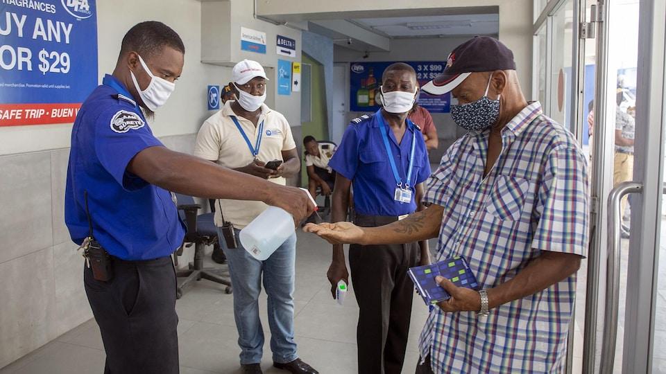 Un agent de sécurité donne du désinfectant à mains à un homme tandis que deux autres les regardent.