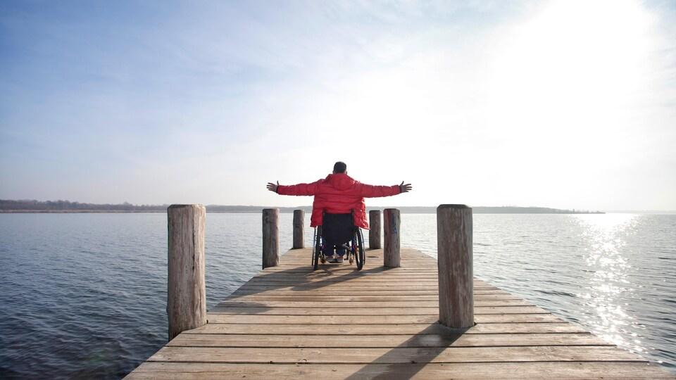 Homme en chaise roulante faisant face à la rivière, ses bras ouverts comme pour embrasser l'immensité.