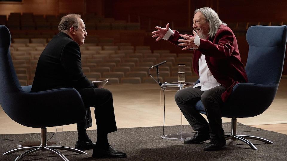 L'animateur Bernard Derome et l'auteur-compositeur-interprète Serge Fiori sont assis sur la scène de la  Maison symphonique de Montréal.