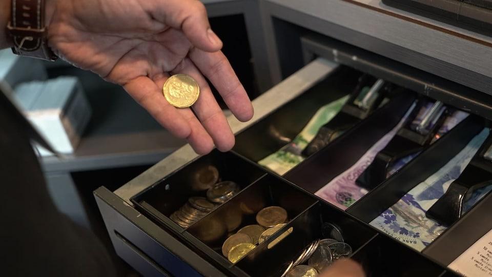 Un caissier dépose une pièce d'un dollar dans une caisse enregistreuse.
