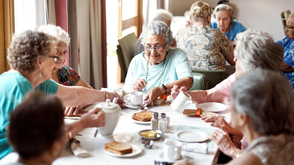 Plusieurs femmes âgées sont assises autour d'une table et prennent un café.