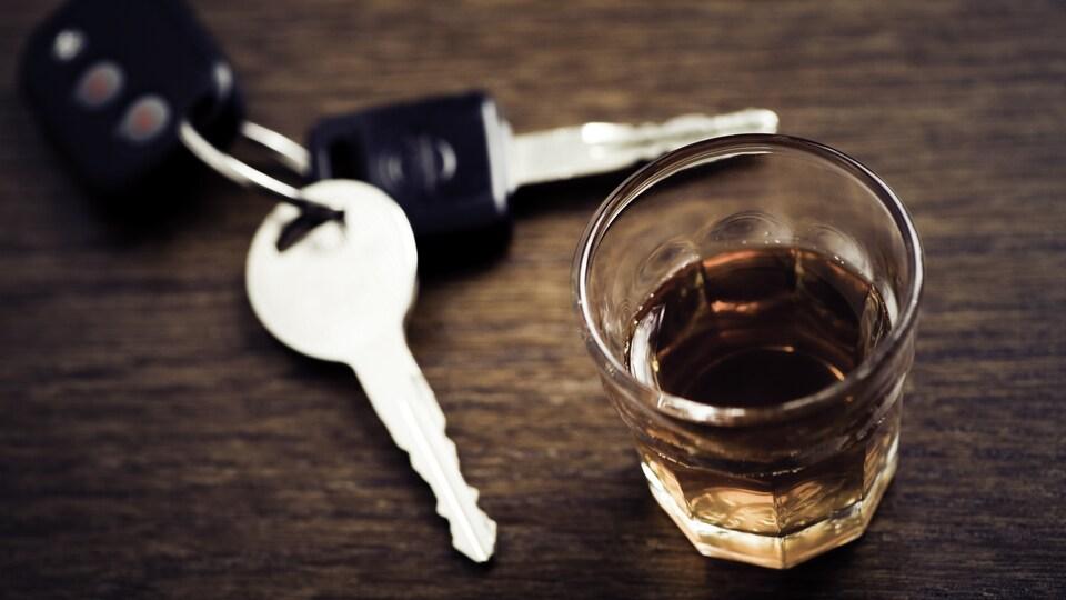 Des clés sont sur une table, posées à côté d'un verre de whisky.