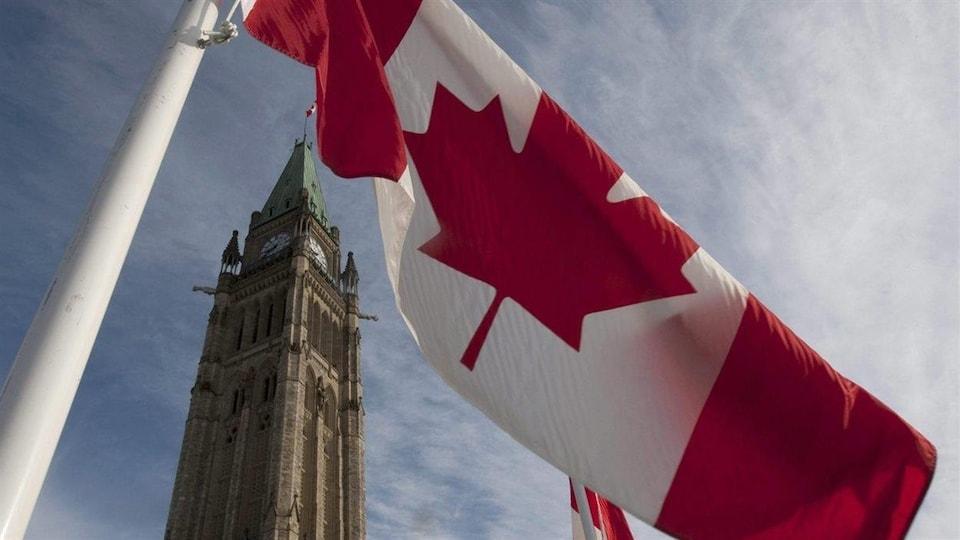 En avant-plan, un drapeau du Canada. En arrière-plan, la Tour de la Paix à Ottawa se découpe sur le ciel.