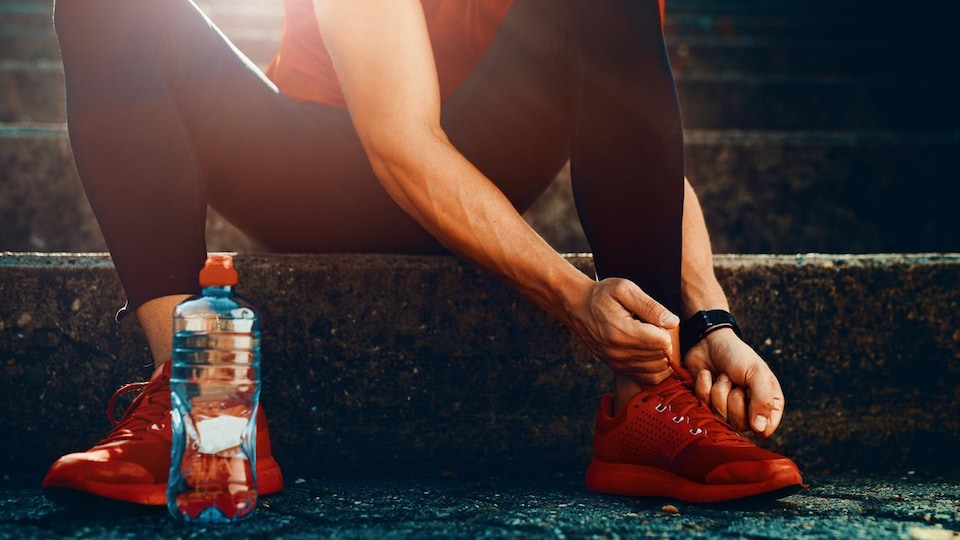 Un homme assis sur des marches à côté d'une bouteille d'eau serre les lacets de ses chaussures de course.