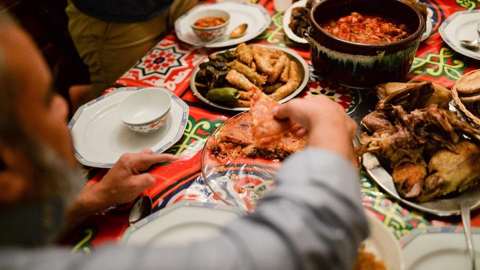 Une main d'homme se sert de la nourriture parmi plusieurs plats disposés sur une table colorée.