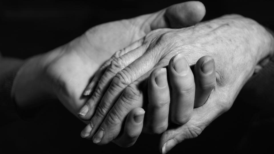 Une main d'une jeune personne qui tient la main d'une aînée.