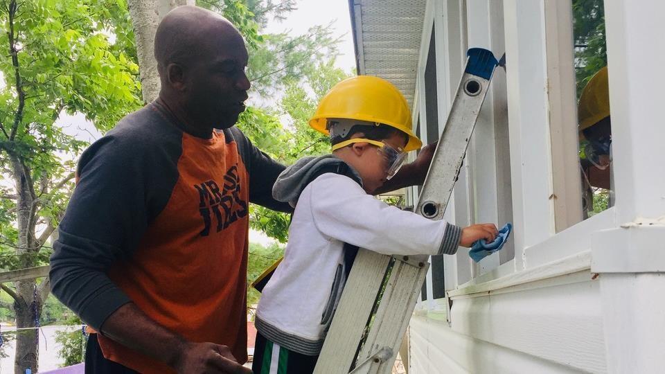 Un enfant nettoie une fenêtre à l'extérieur aidé par un homme.