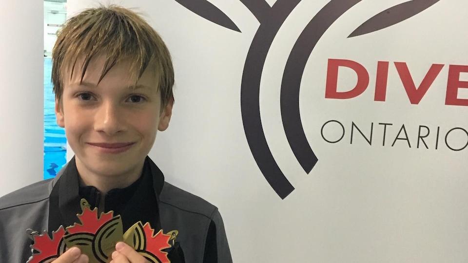 Noland Léger Lazary montre ses médailles après une compétition de plongeon