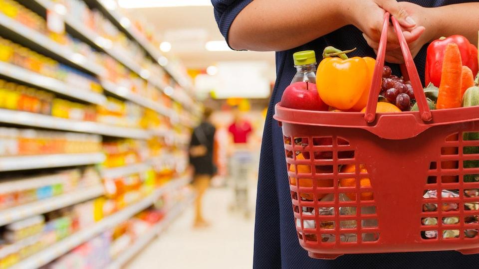 Une femme tient un panier de fruits et légumes dans une allée d'épicerie.