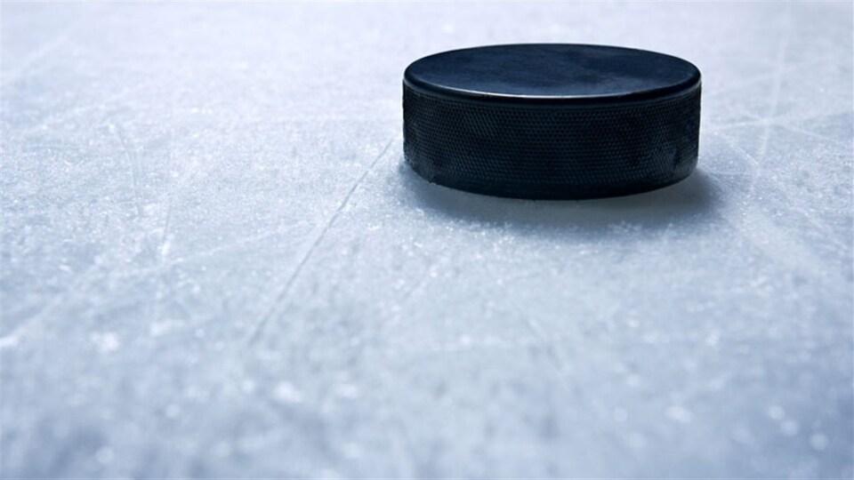 Une rondelle de hockey en gros-plan sur la glace d'un patinoire.