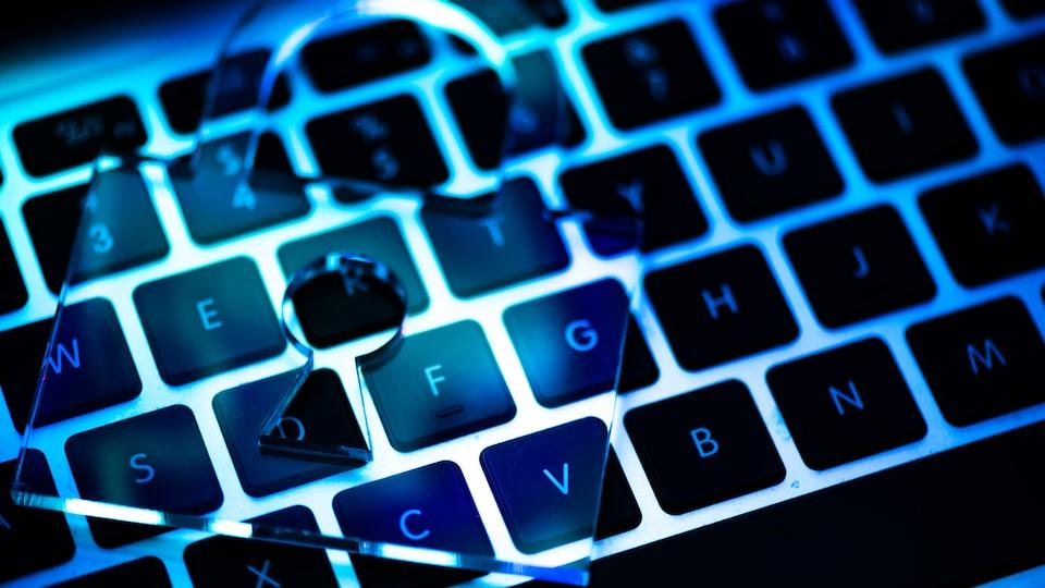 Un gros plan du clavier d'un ordinateur avec un cadenas transparent déposé dessus.