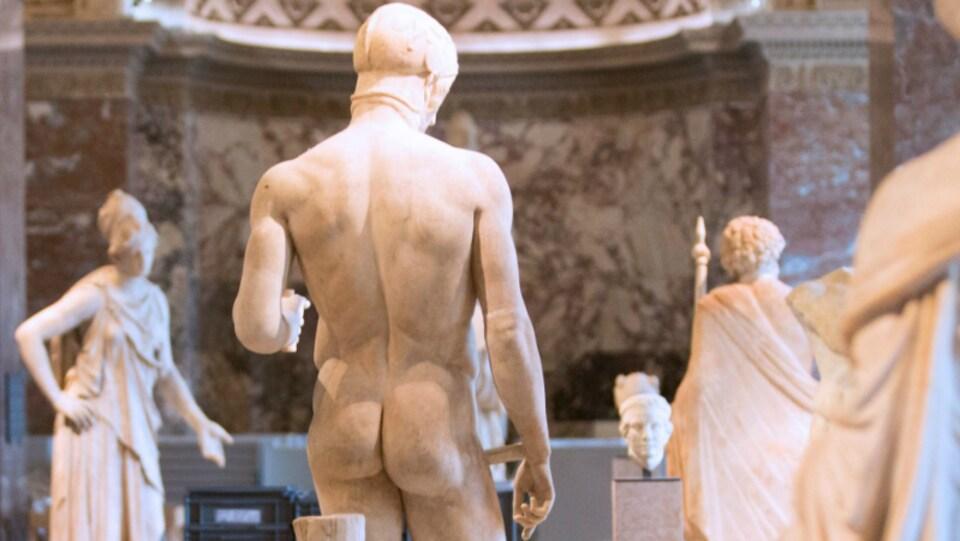 Des statues grecques dont une de dos, nue.