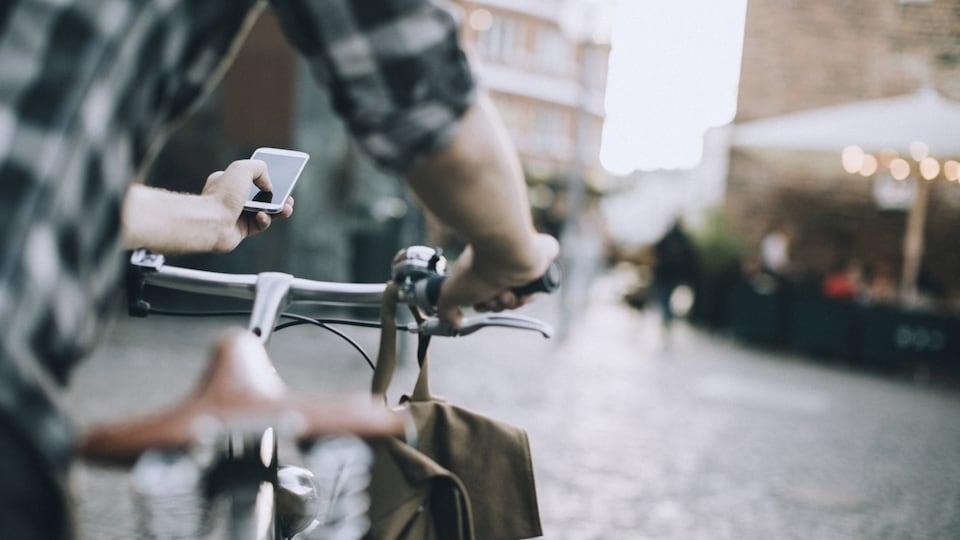 Un cycliste utilise son téléphone portable alors qu'il se trouve à côté de sa bicyclette. Il se trouve sur une place publique.