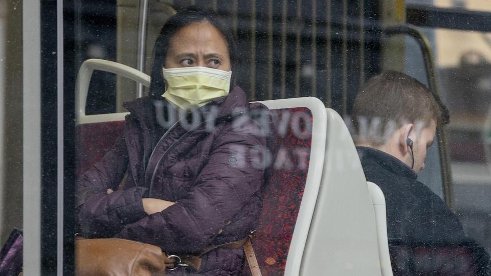 Une femme porte un masque, assise dans un tramway.