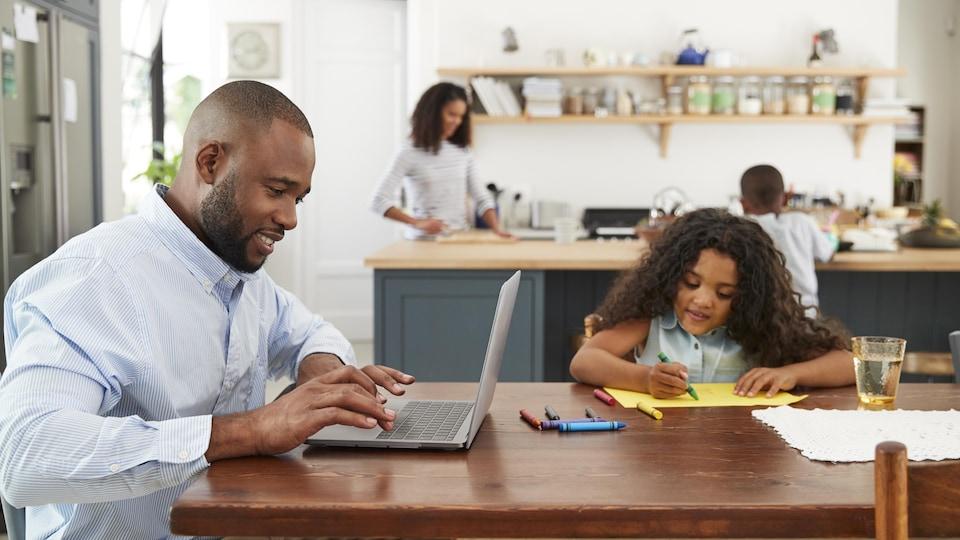 Un homme travaille sur un ordinateur à la table de sa cuisine en compagnie de sa fille.